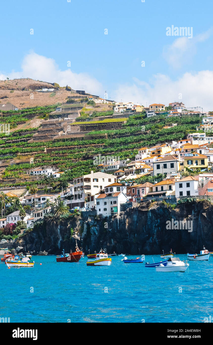 Fisherman village Camara de Lobos in Madeira Island, Portugal photographed from the waters of the Atlantic ocean. City on a mountain by the coast. Tourist places. Banana plantations on the hill. Stock Photo