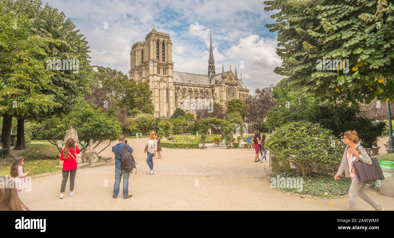 tourists posing and taking photographs at square rene viviani with notre dame cathedral in background Stock Photo