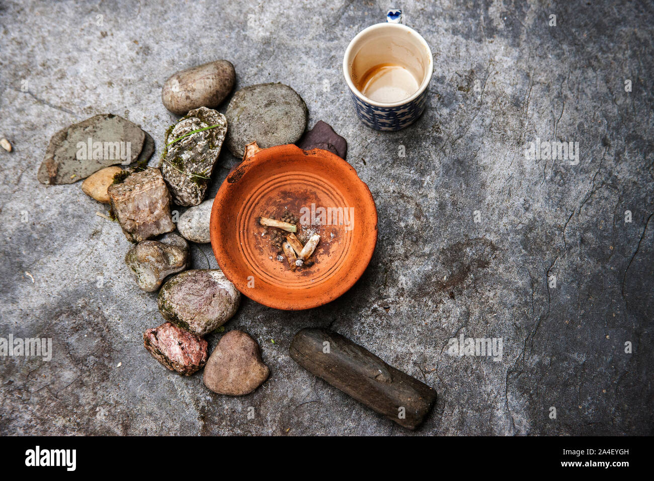ashtray with roll up cigarettes on slate beside rocks and coffee mug Stock Photo