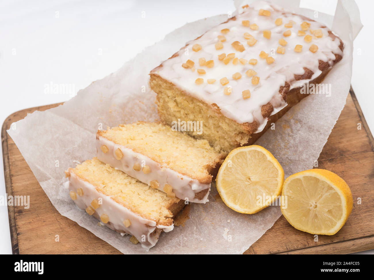 Sliced homemade iced and decorated lemon drizzle cake on a wooden chopping board. Stock Photo