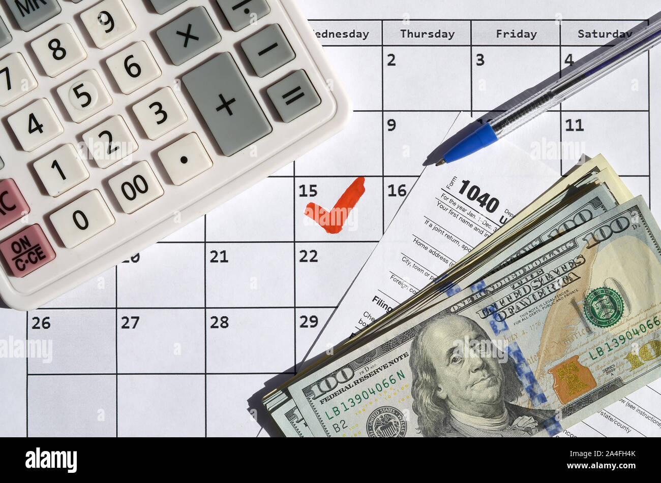1040 Individual Income Tax Return blank with dollar bills, calculator and pen on calendar page with marked 15th April. Tax period concept. IRS Interna Stock Photo