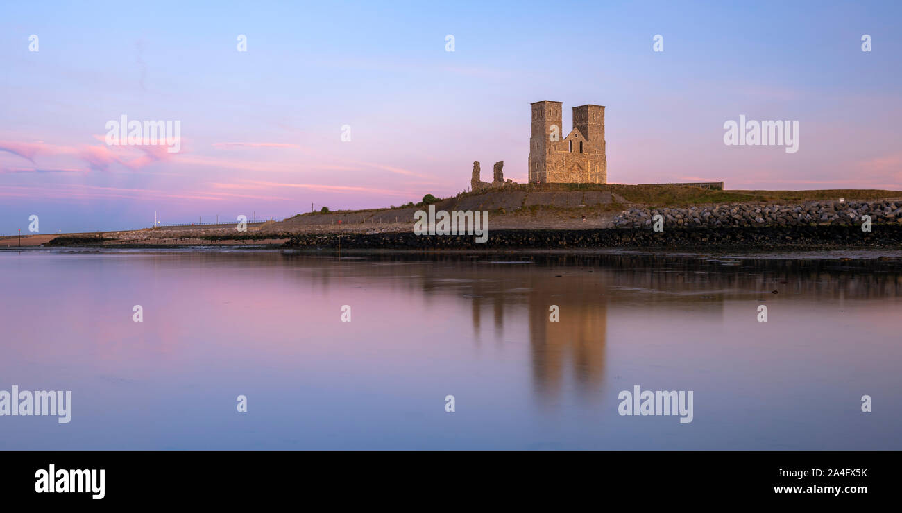 Reculver Towers; a medieval church and site of a Roman fort reflected in the low tide at sunset. Stock Photo