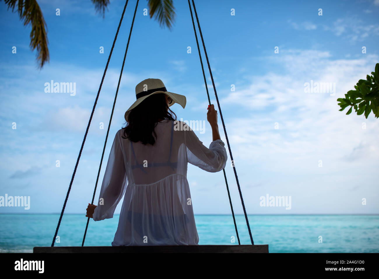Young beautiful woman relaxing in swing hanging on coconut palm at exotic beach.Blue sea and white sand. Fashion girl enjoying on seashore. Brunette g Stock Photo