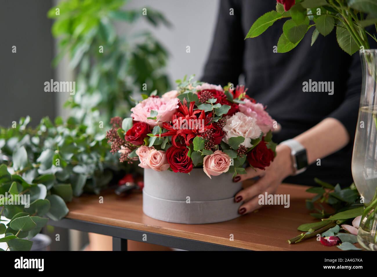 Floral shop concept . Florist woman creates flower arrangement in a round box. Beautiful bouquet of mixed flowers. Handsome fresh bunch. Flowers Stock Photo
