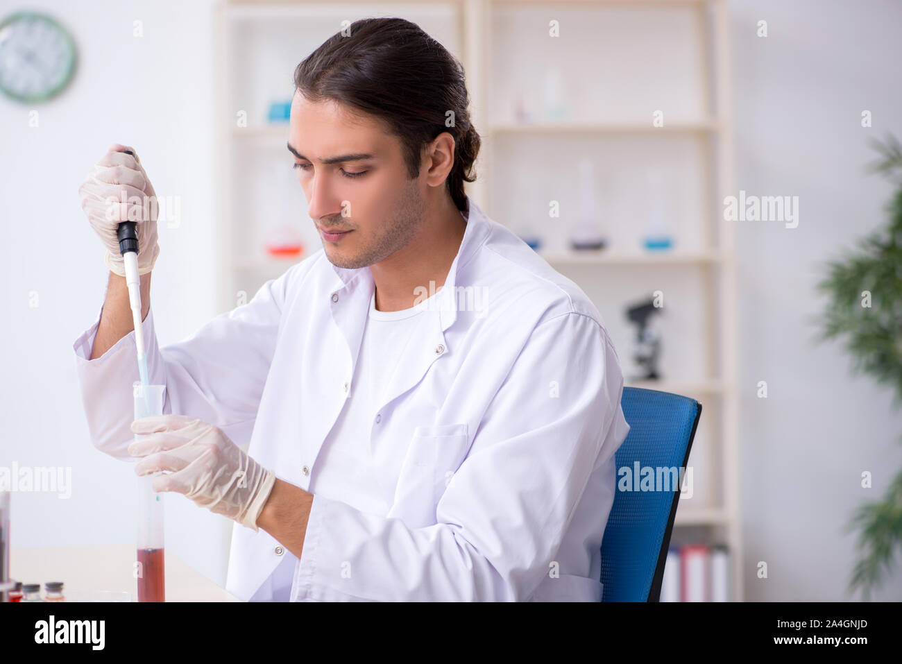 The young male chemist working in the lab Stock Photo