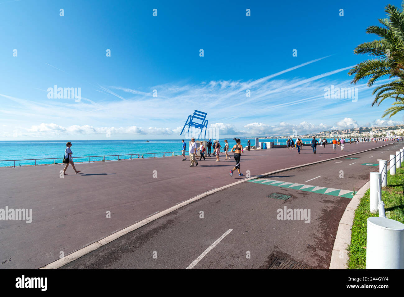 Joggers and walkers pass by the Blue Chair balancing along the Promenade des Anglais on the French Riviera in Nice France along the Mediterranean Sea. Stock Photo