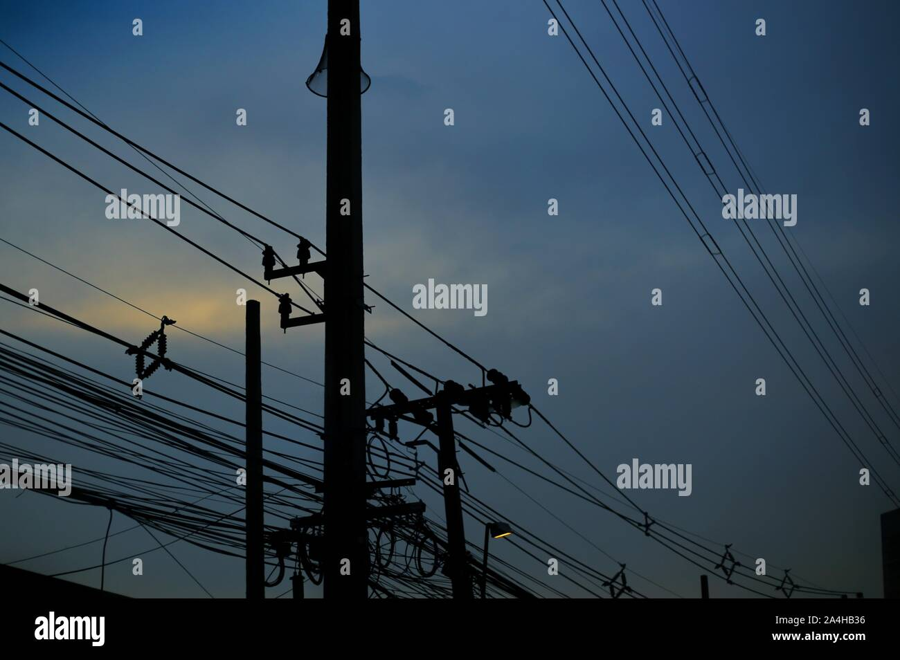 electrical power and telecommunication lines silhouette. blue hour after sunset. irregular and chaotic arrangement pattern. unordered poor design of t Stock Photo