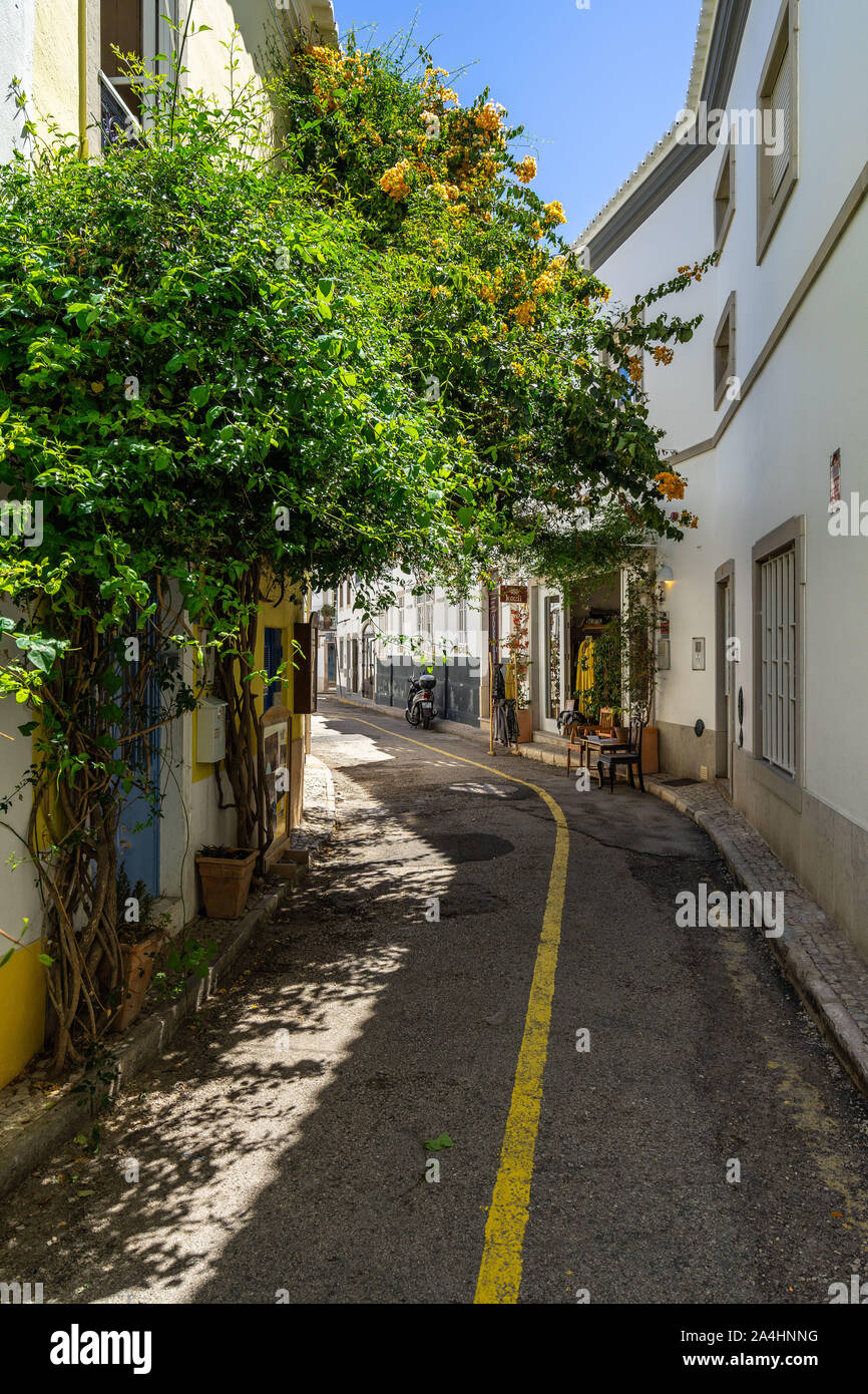 Picturesque street in Tavira old town decorated with flowers. Tavira, Algarve, Portugal, April 2019 Stock Photo