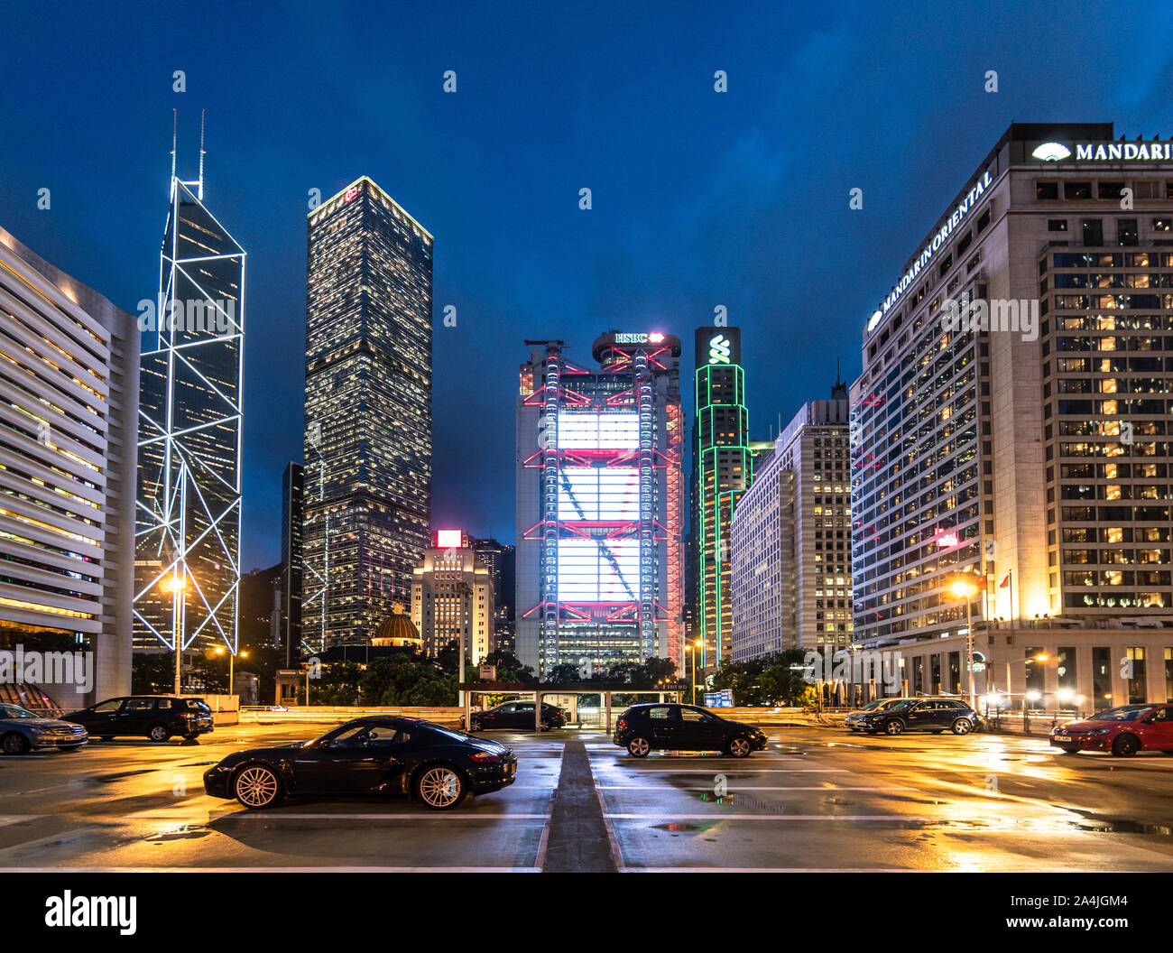 Hong Kong - China - July 4 2019: Luxury sport cars parked on a rooftop parking in Hong Kong Central business district with major bank office building Stock Photo
