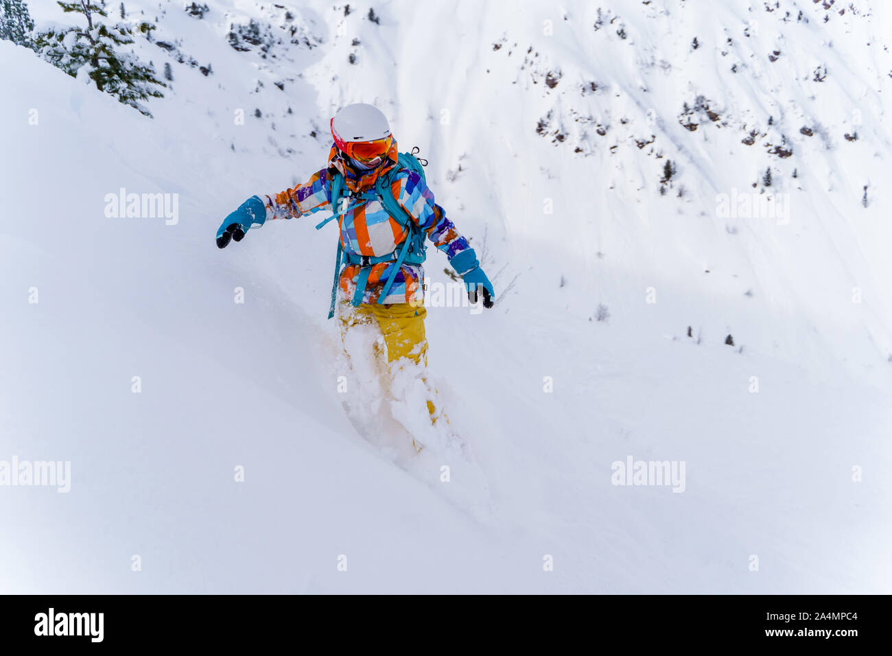 Young athlete girl in helmet and mask is riding on snowboard on snowy slope at winter day. Stock Photo