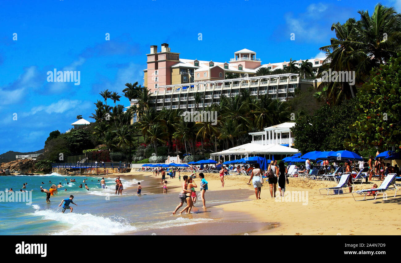 St. Thomas , Virgin Islands - 18, February 2015: Tourists enjoying a beautiful day on a beach in St. Thomas Virgin Islands with hotel on hill above. Stock Photo