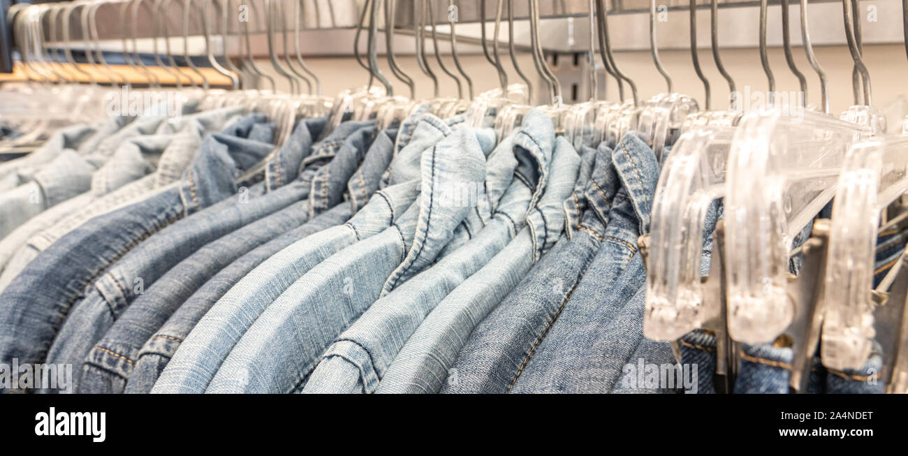 Male mens denim jeans shirts sorted on clothes hangers on a shop wardrobe closet Stock Photo