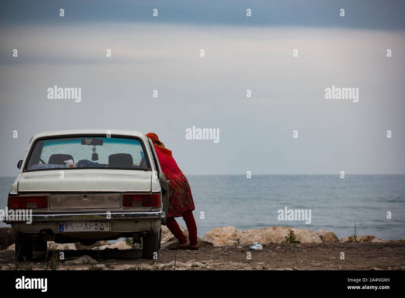 Here is Caspian sea in Mazandaran city northern of Iran. A deparate lonely Muslim woman is leaning to her husband`s car and looking at the sea horizon Stock Photo