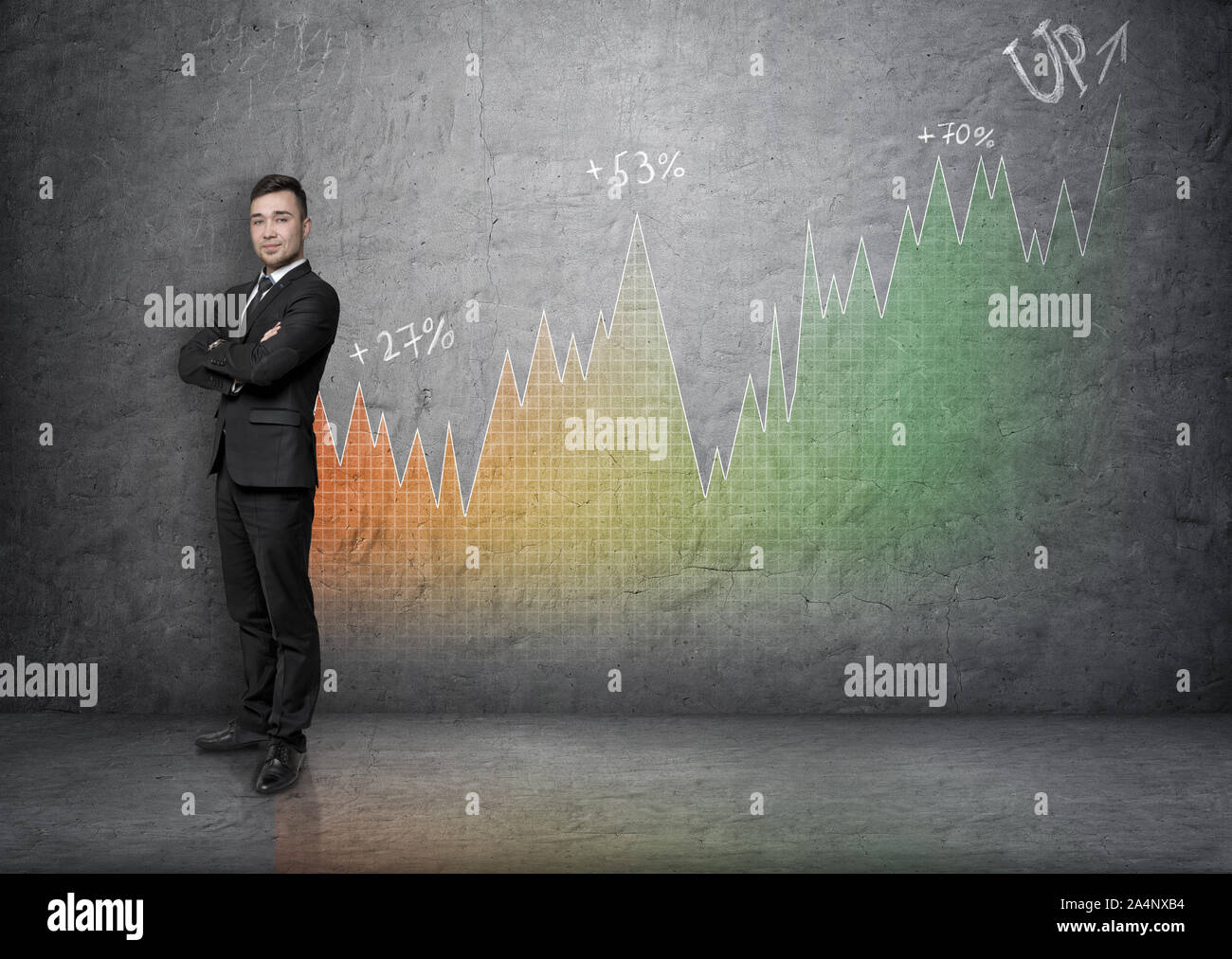 Full portrait young businessman with his arms crossed on background of an increasing graph Stock Photo
