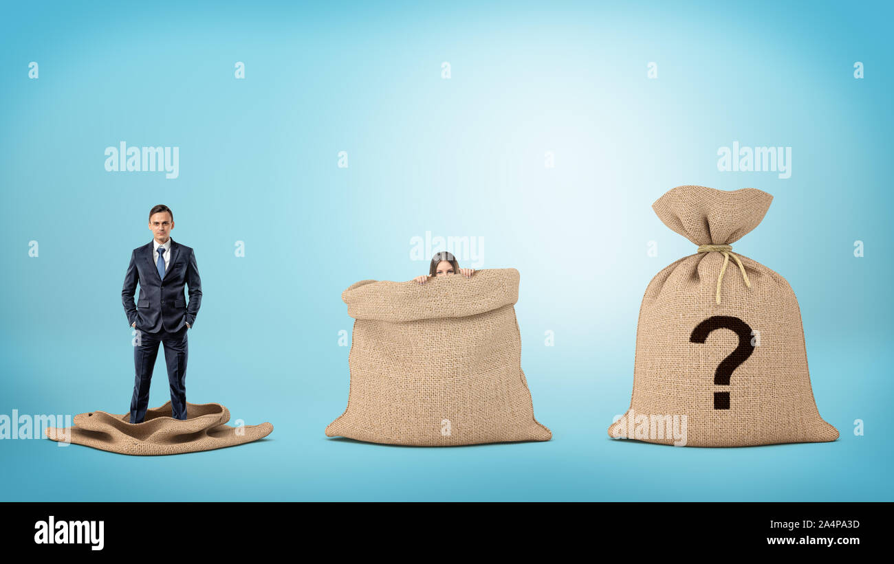 A businessman in an empty sack and a woman behind an open sack, and one sack closed with a question mark. Stock Photo