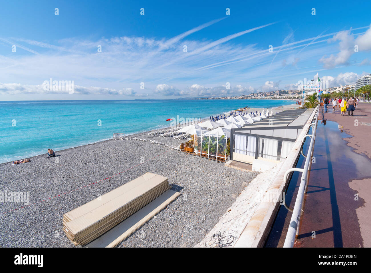 A private beach club with white umbrellas and lounges on the beach of the French Riviera at Nice France Stock Photo
