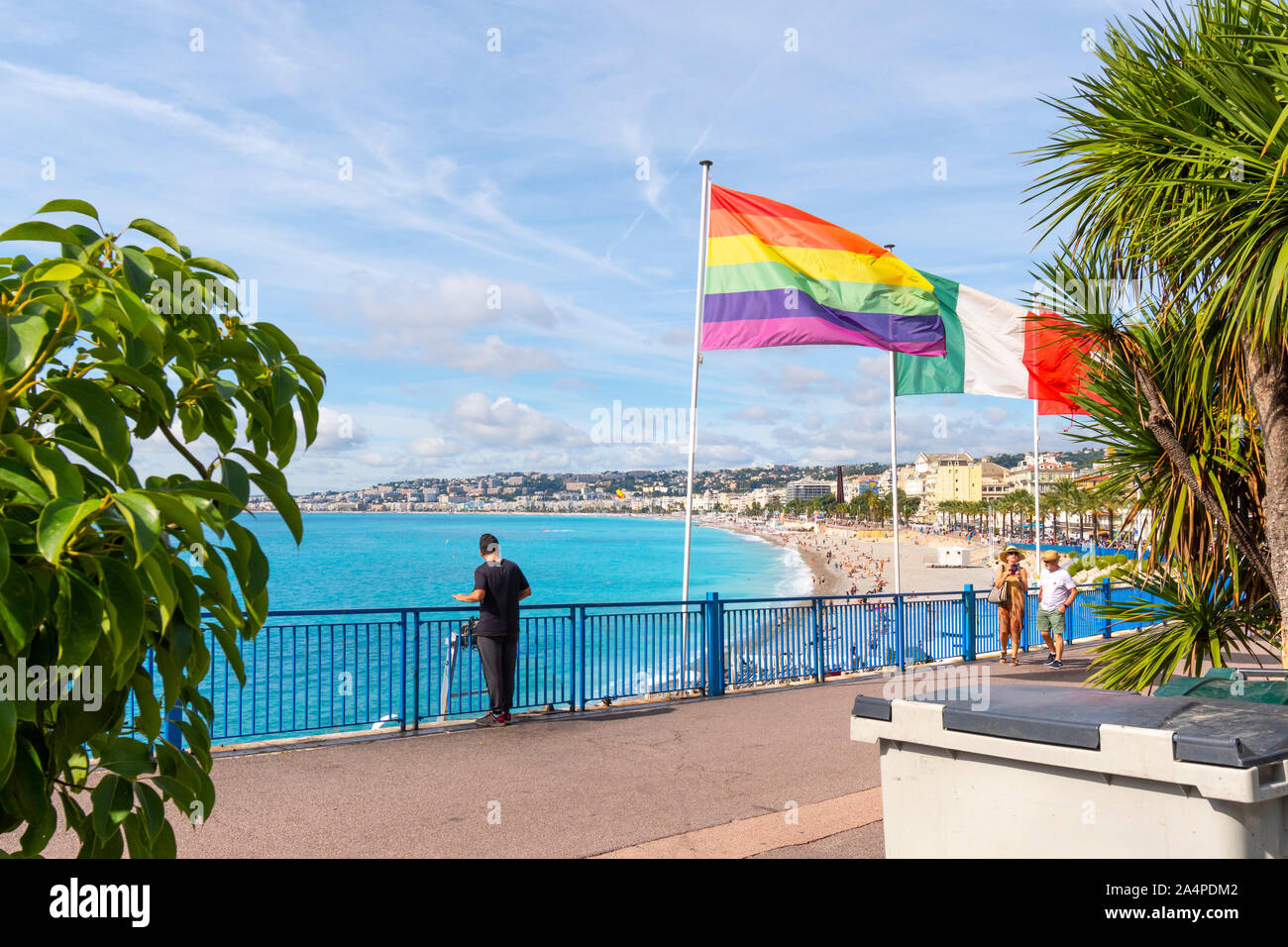 Tourists enjoy a beautiful day near the Rainbow flag on the French Riviera near Castle Hill overlooking Bay of Angels and the beach in Nice Stock Photo