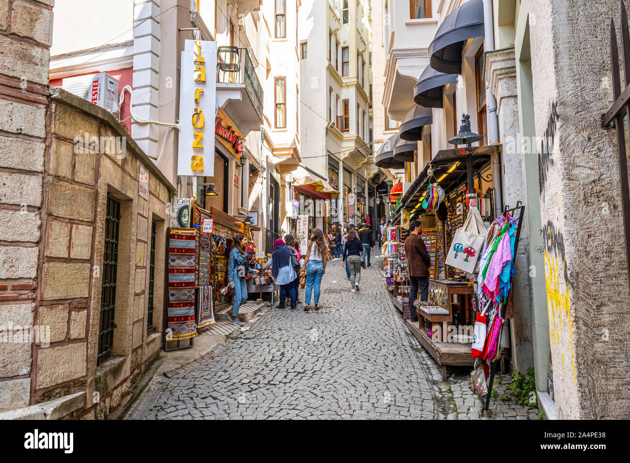 Local Turks including a group of younger girls go shopping on a colorful hilly street in the Galata Karakoy district of Istanbul, Turkey Stock Photo
