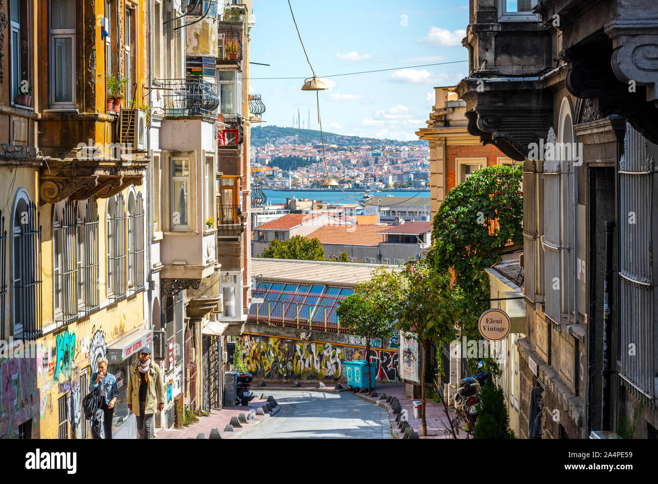 A couple walks the hilly Galata Karakoy district with the Bosphorus River and Golden Horn in the distance in Istanbul, Turkey. Stock Photo