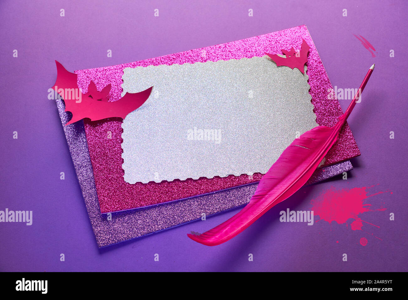 Creative Halloween background in glowing neon pink and purple with stack of glittering paper, quill and paper bats. Copy-space on the top card. Stock Photo