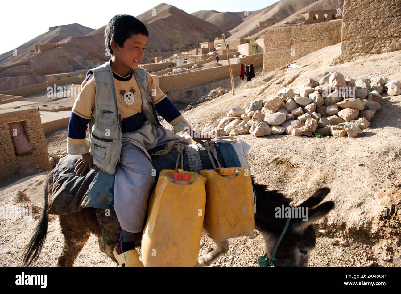 A boy transports water for his family on a donkey, in the village of Rag-e-shad, in central Bamyan province, Afghanistan. May 11, 2009. Stock Photo