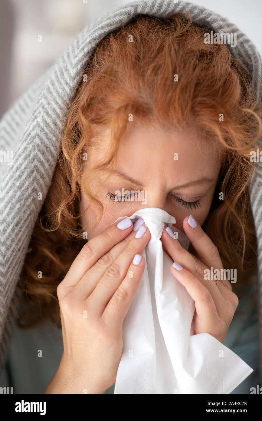 Woman covered in plaid taking napkin while having stuffy nose Stock Photo