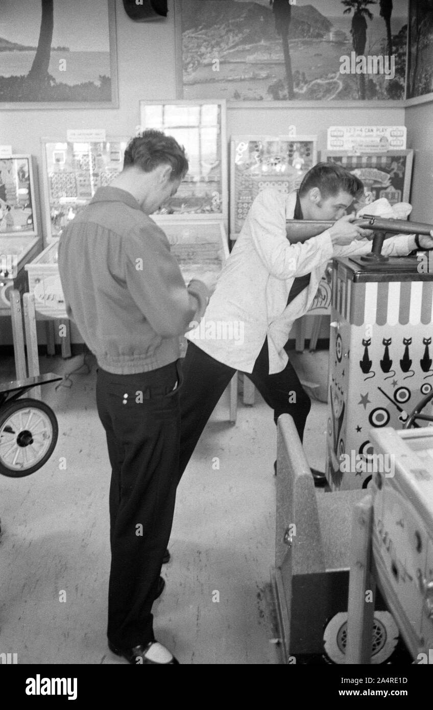 Elvis Presley in an arcade with Gene Smith. The precise location is uncertain, but the arcade was in Detroit, Michigan, and Elvis was relaxing in between shows at the Fox Theater on May 25, 1956. The arcade was likely very close to the theater. Stock Photo