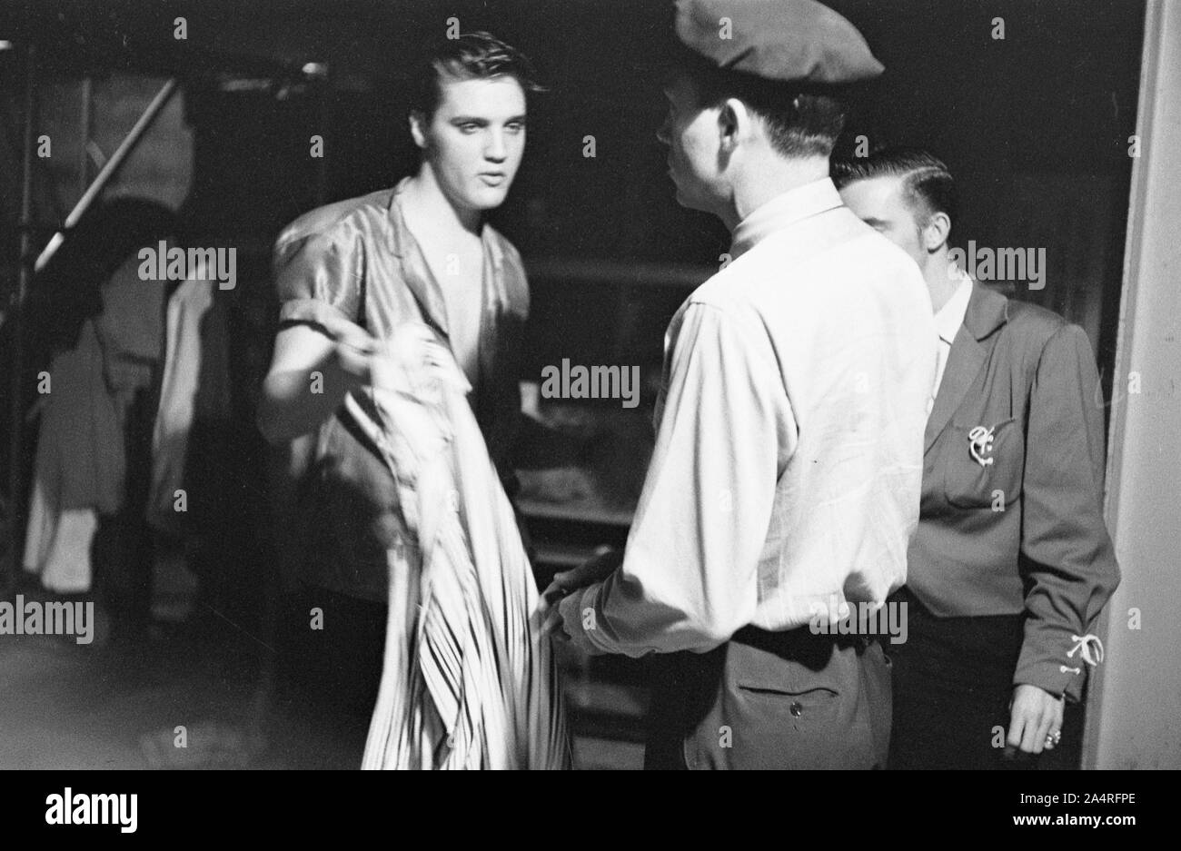 """Elvis Presley and his cousin Gene Smith, backstage at the University of Dayton Fieldhouse, May 27, 1956. Gene Smith was part of Presley's entourage, and is considered a member of the """"Memphis Mafia"""". Stock Photo"""