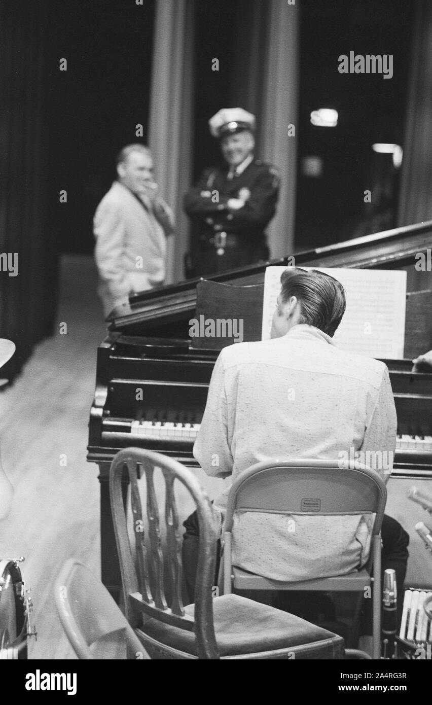 Elvis Presley waiting for a show to start, playing piano, at the University of Dayton Fieldhouse, May 27, 1956. Stock Photo