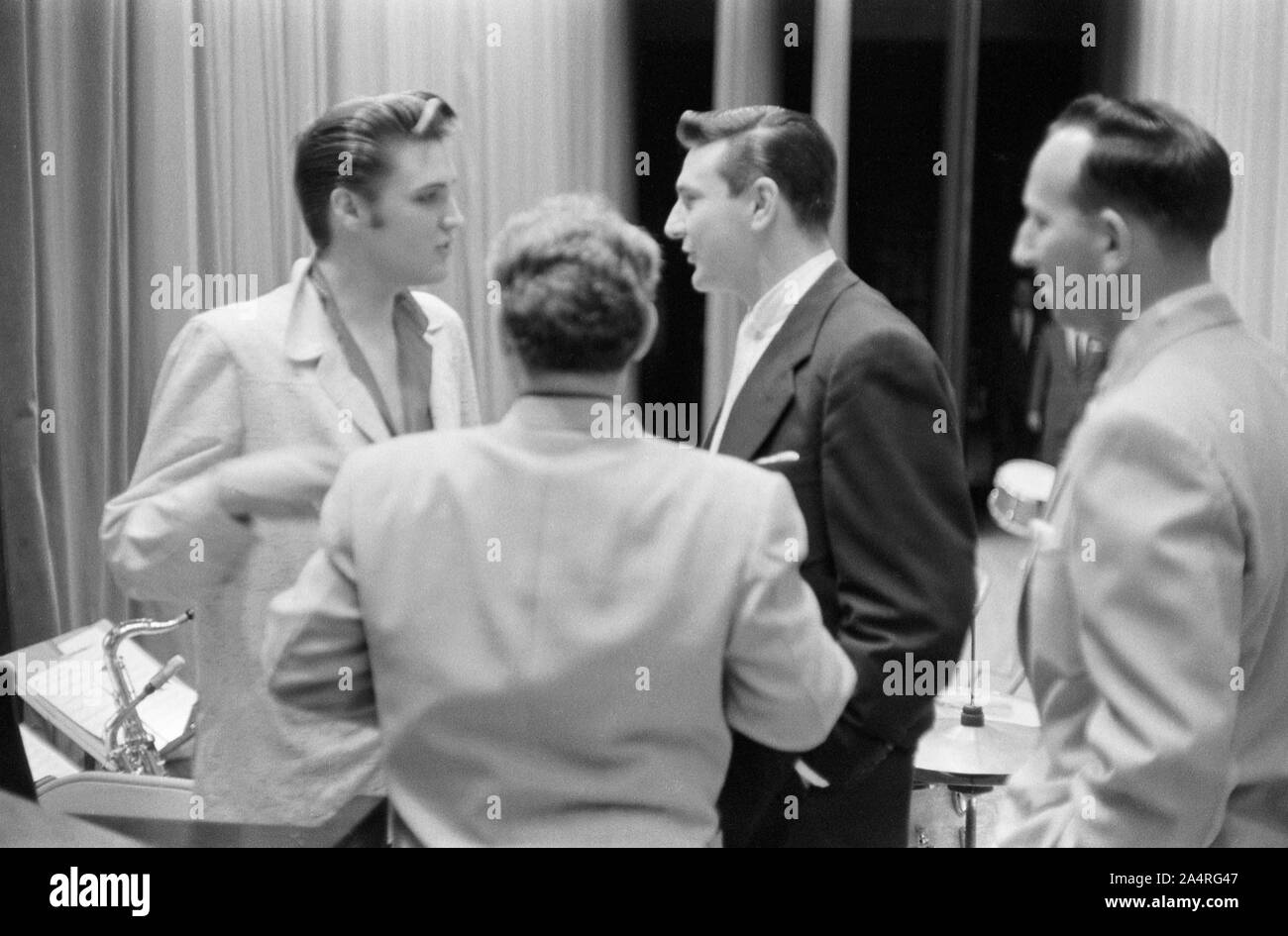 Elvis Presley speaking with several men, probably music industry executives, while waiting for a show to start at the University of Dayton Fieldhouse, May 27, 1956. Stock Photo