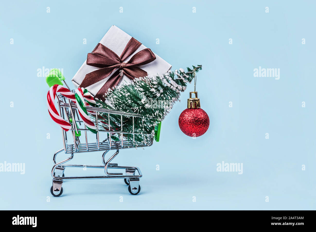 Christmas Tree Gift Box And Candy Canes In Miniature Shopping Cart With On Pastel Blue Background With Copy Space Stock Photo Alamy