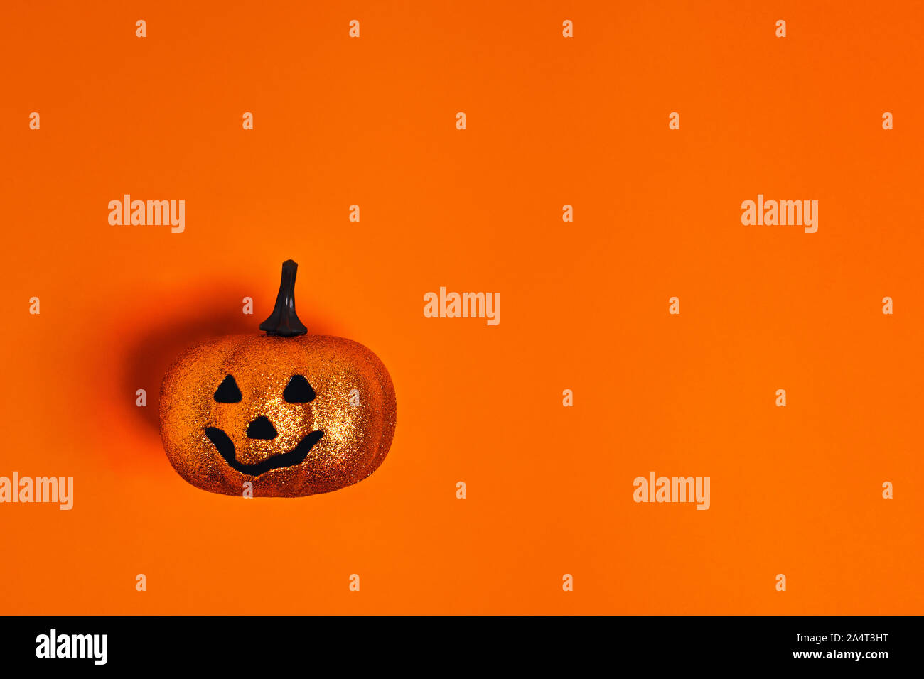 Halloween decoration concept - orange background with decorative pumpkin. Flat lay, top view. Place for your text. Stock Photo