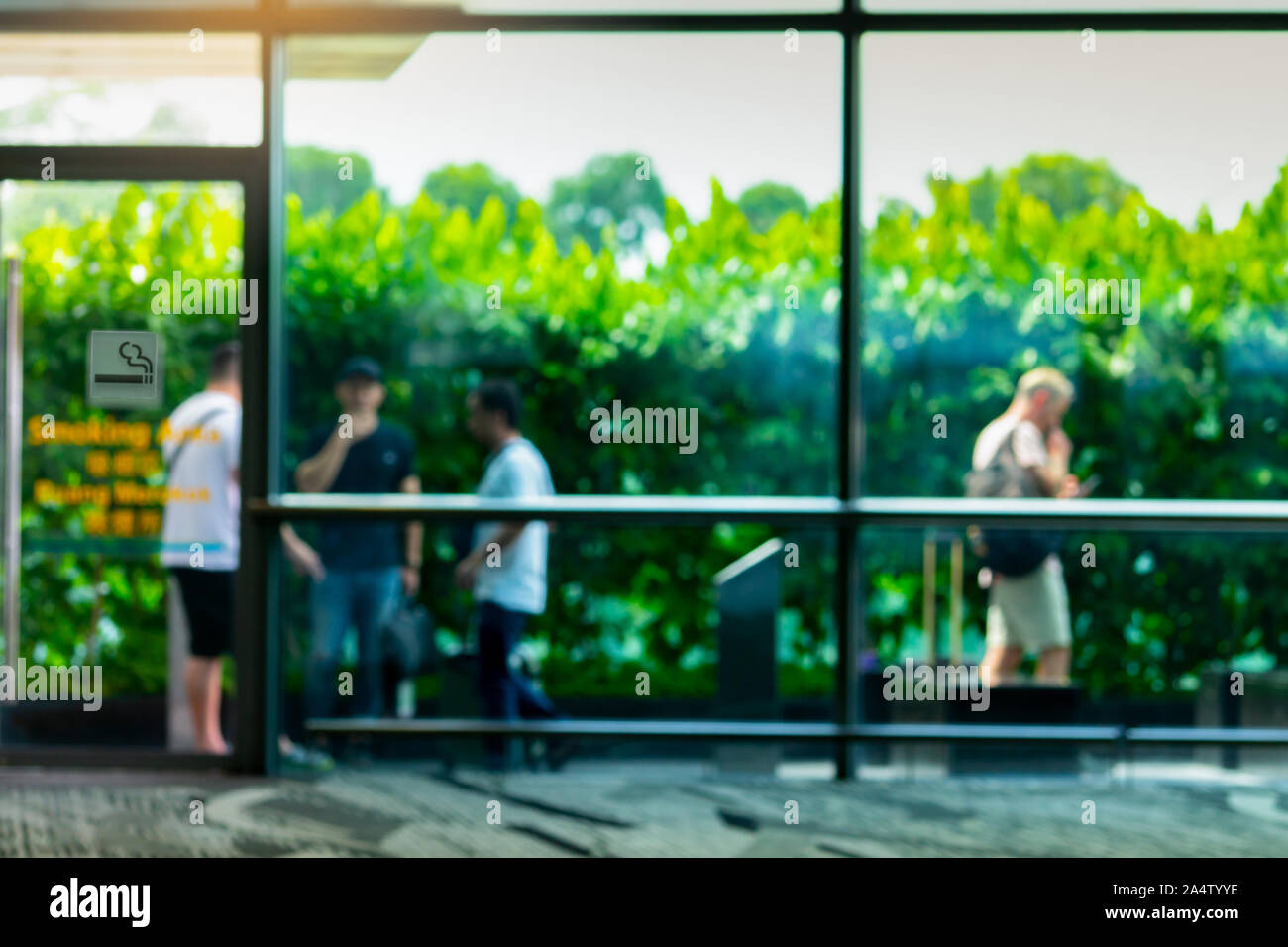 Blurred people smoking in smoking zone area of the mall or office. Four man smoke in smoking area beside green wall of tree. Quit smoke or smoking Stock Photo