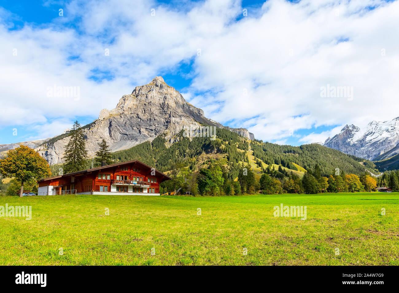 Wooden chalet in Kandersteg village, Canton Bern, Switzerland, Europe, Autumn trees and mountains panorama Stock Photo