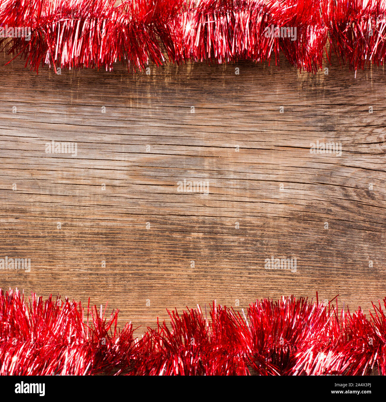 Old wooden boards framed by red tinsel. New Year, Christmas background with space for text. Stock Photo