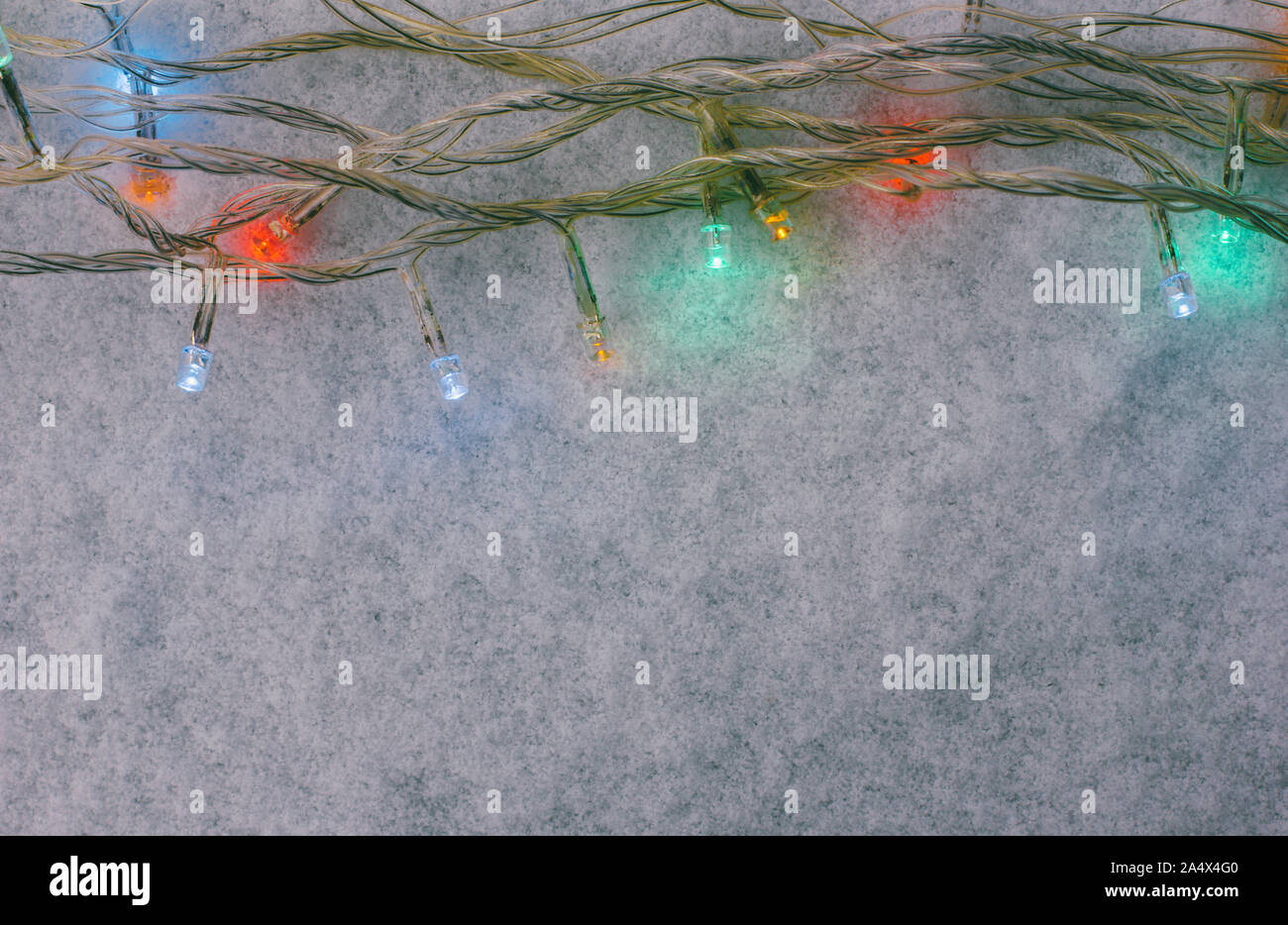 Christmas or new year background with multicolored Christmas lights on snow with space view, top view Stock Photo