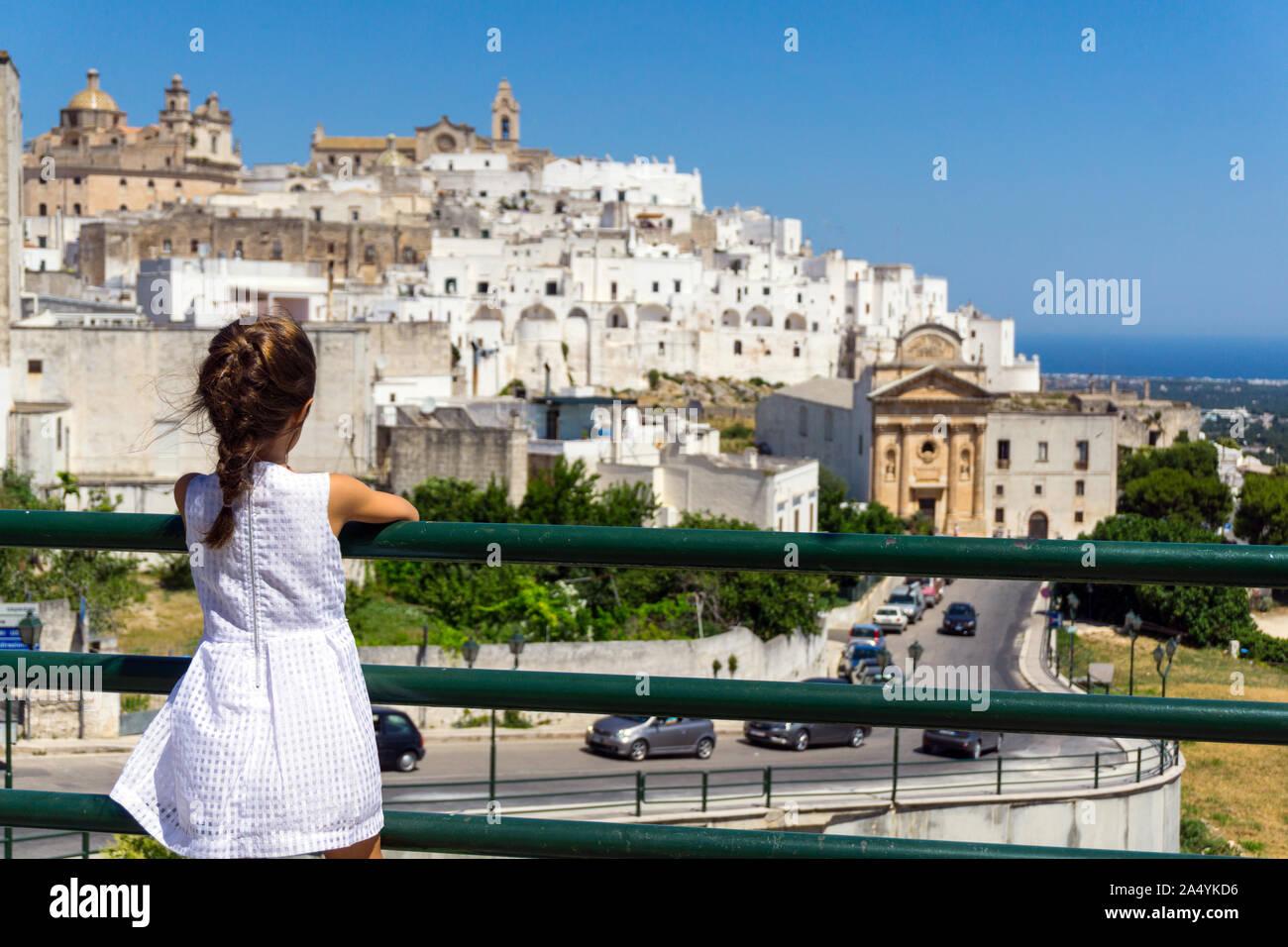 Italy, Apulia, Ostuni, little girl looking old town cityscape Stock Photo