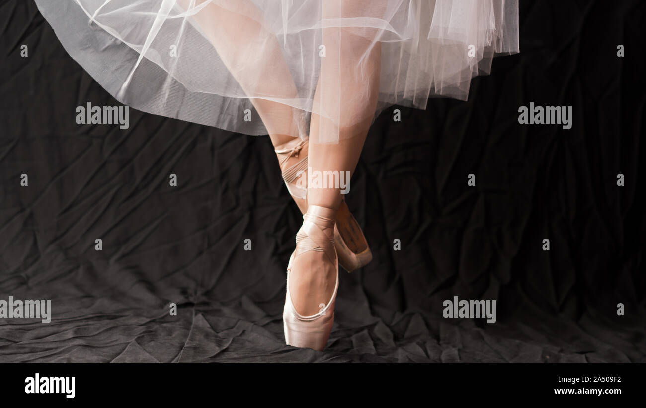 Close-up of dancing legs of ballerina wearing white pointe on a black background. Ballet dancer and practice concept background Stock Photo