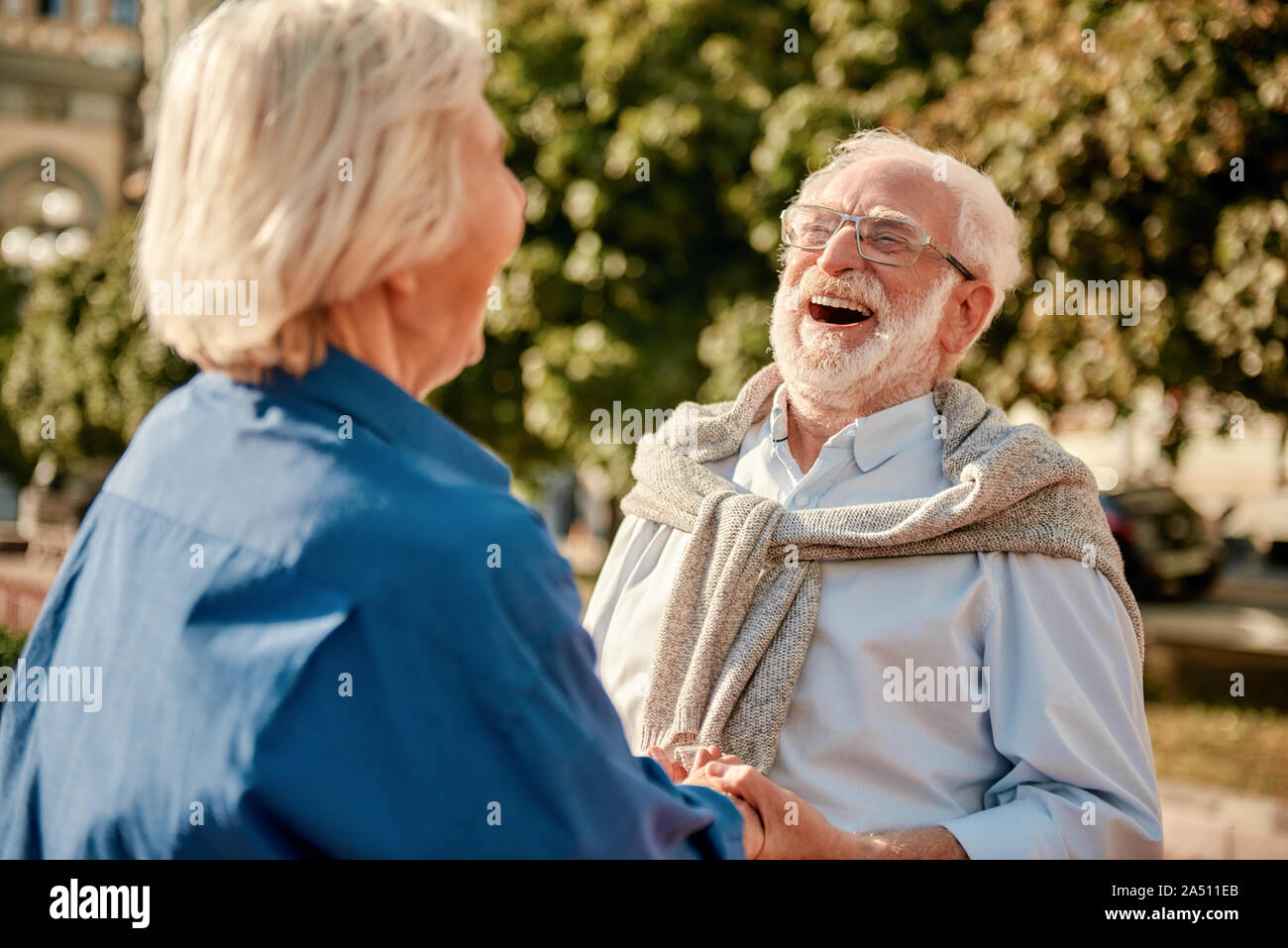 So funny! Happy and beautiful elderly couple holding hands and laughing while standing outdoors Stock Photo