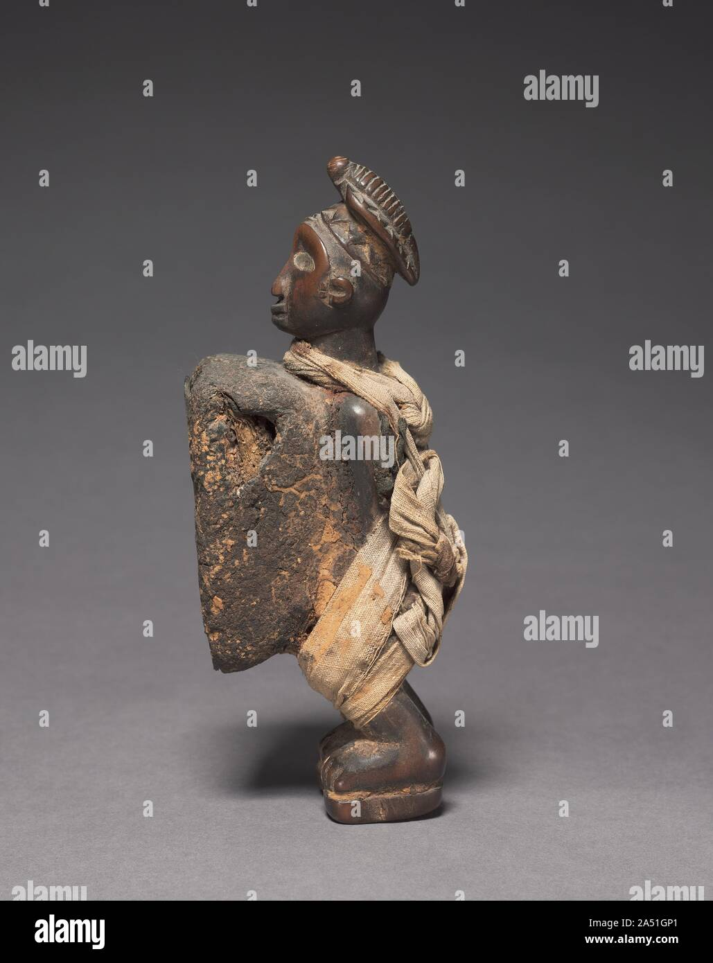 Male Figurine, late 1800s-early 1900s. This human-shaped  nkisi  in Yombe style—one of the most typical forms a spirit container can take among Kongo speakers in west-central Africa—features an enormous mirror-covered package on its stomach that is remarkably intact, meaning that the figure was not decommissioned before sale or disposal. The cloth bands and knots looped around its neck and down its back and fixed around its legs suggest that it was used to bind agreements or oaths. Most intriguing is the carving of a pangolin or scaly anteater atop the head, which represents lead Stock Photo