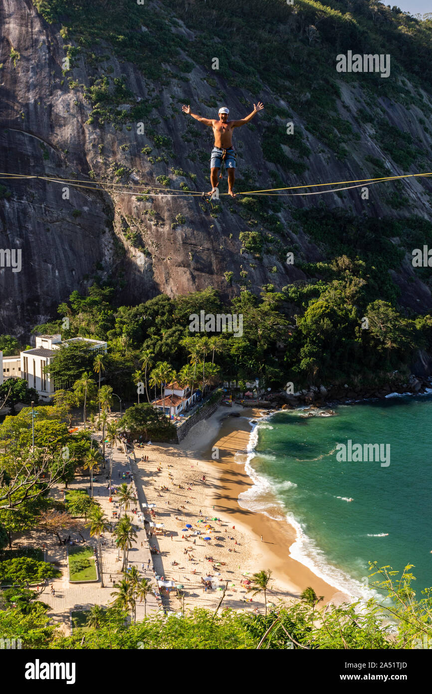 Slackliner walking on highline with beautiful landscape and Sugar Loaf Mountain on the back, Rio de Janeiro, Brazil Stock Photo