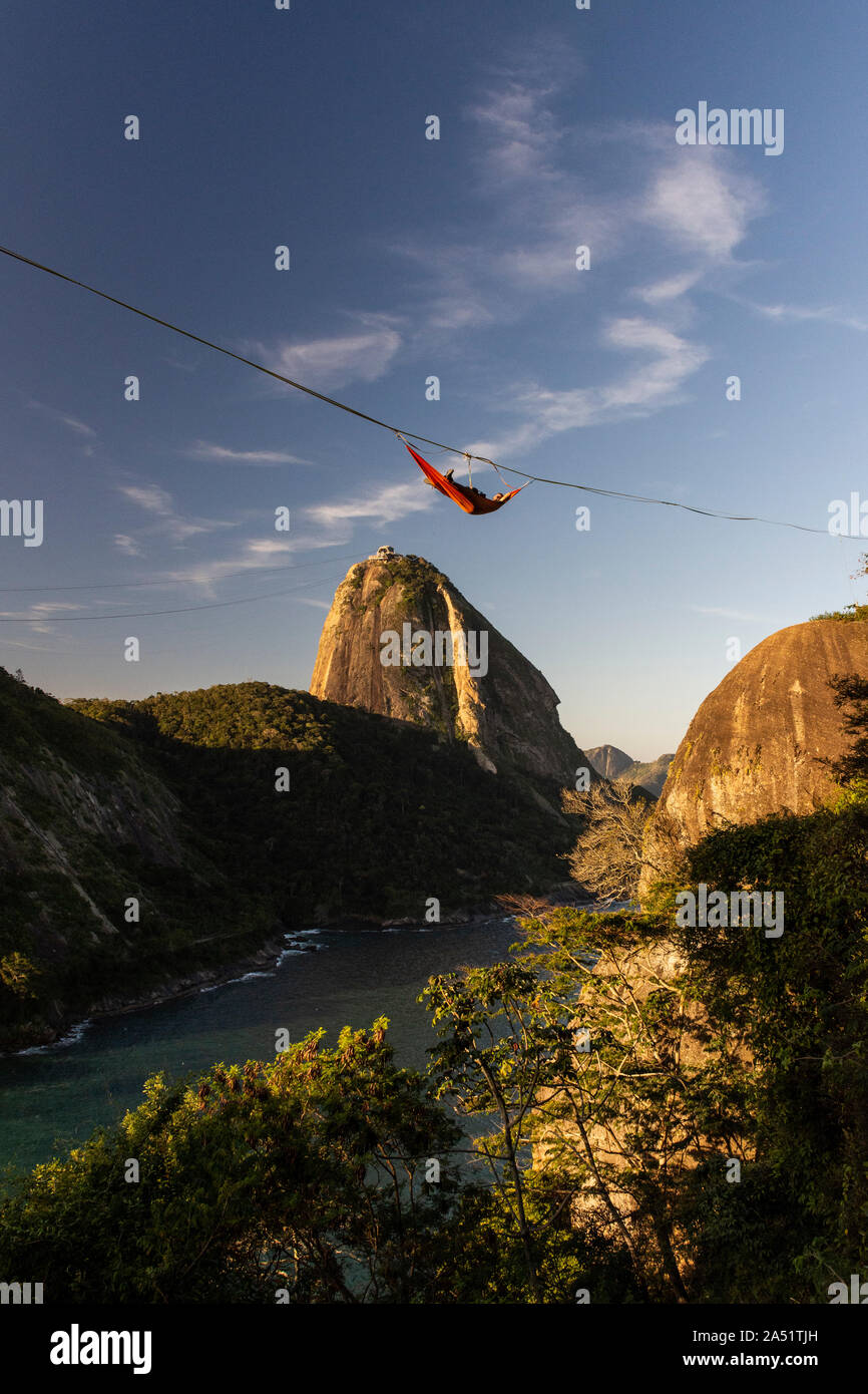 Slackliner resting on climbing net hanging from highline with Sugar Loaf Mountain on the back, Rio de Janeiro, Brazil Stock Photo