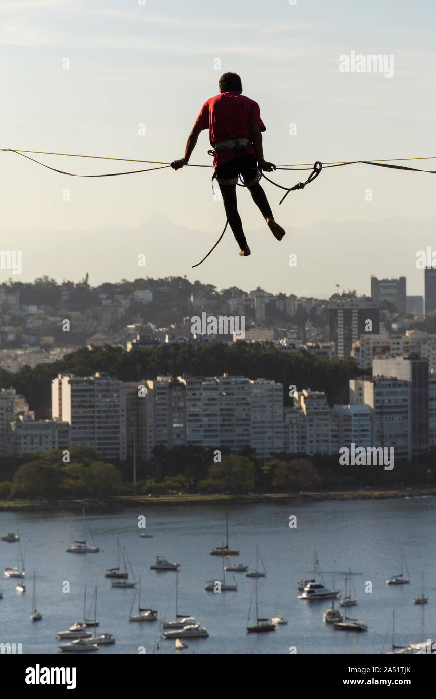 Slackliner walking on highline with ocean, city buildings and mountains on the back, Rio de Janeiro, Brazil Stock Photo