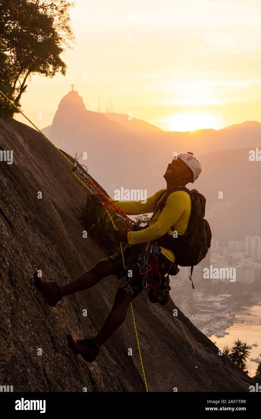 Man on rappel after rock climbing on the Sugar Loaf, Christ the Redeemer on the back, Rio de Janeiro, Brazil Stock Photo