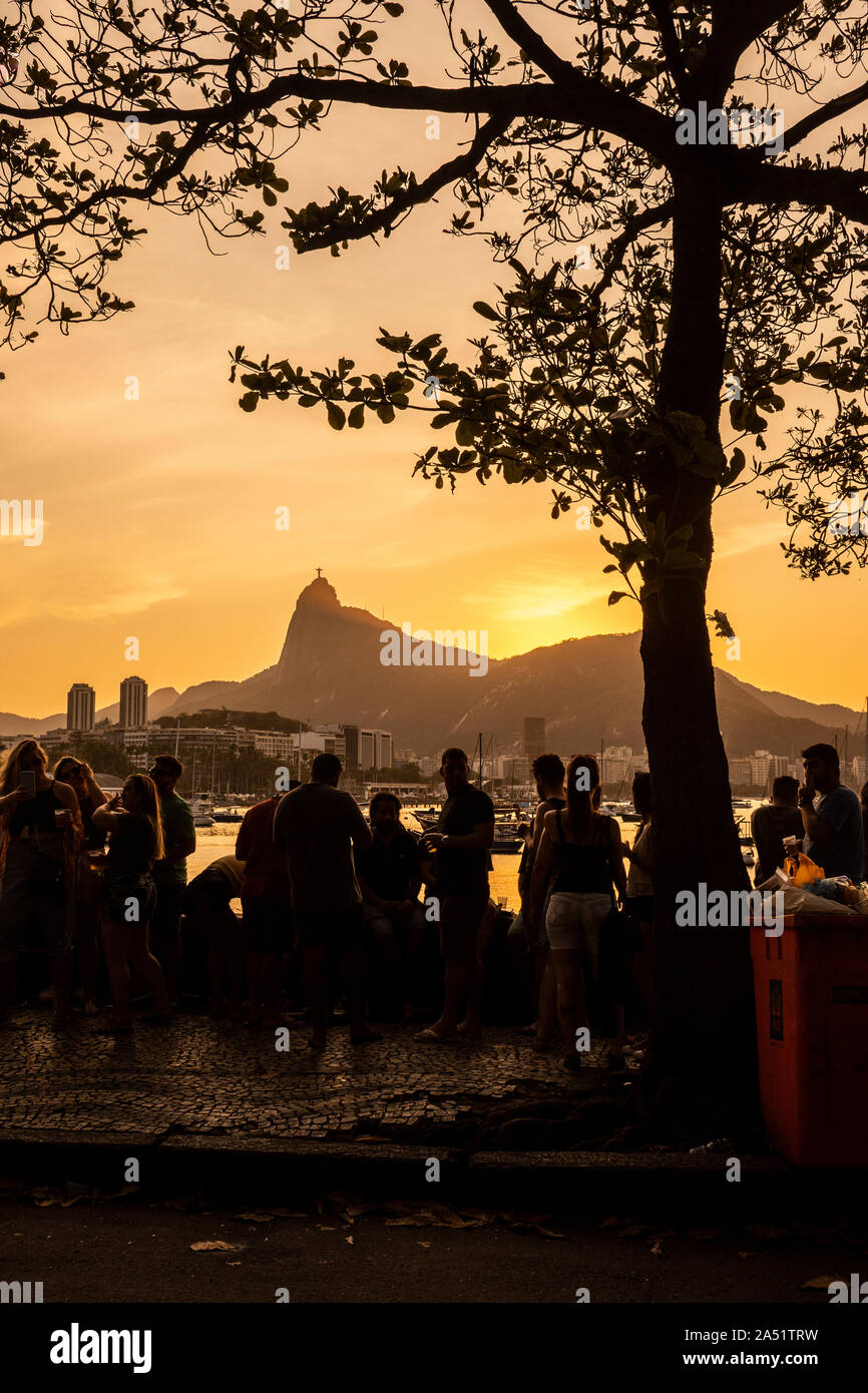 Beautiful sunset view of friends socializing and drinking by the ocean walk in Mureta da Urca with Corcovado Mountain on the back, Rio de Janeiro, Bra Stock Photo