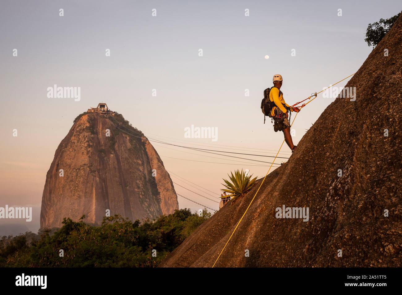 Man rock climbing in Morro da Urca near the Sugar Loaf Mountain, Rio de Janeiro, Brazil Stock Photo