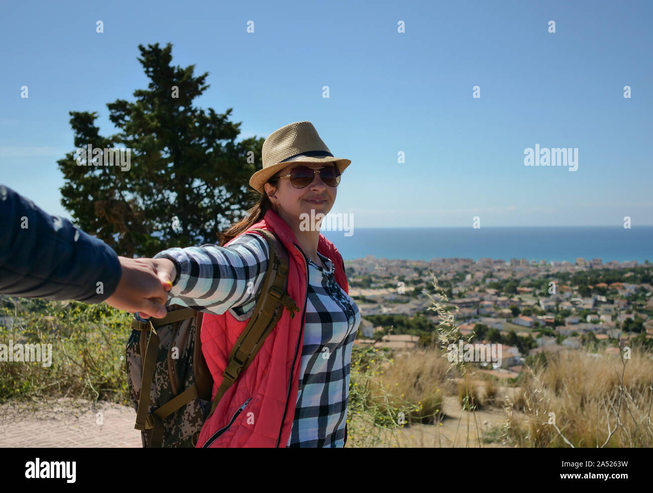 Attractive young woman tourist with a backpack on nature leads a guy by the hand. follow me Stock Photo