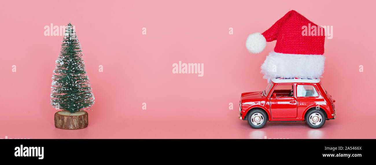 Changxing, China - October 15, 2019: Red toy car with a santa hat, next christmas tree on pink paper background. Winter delivery, xmas, happy new year Stock Photo