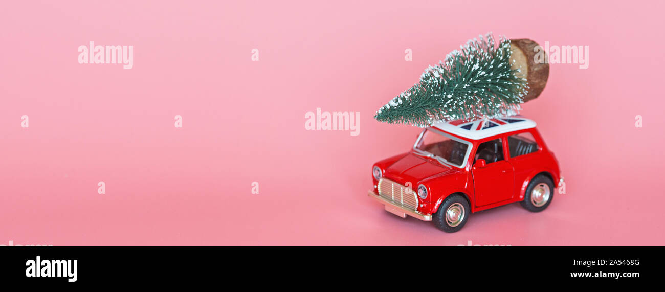 Changxing, China - October 15, 2019: Red toy car with a christmas tree on the roof on pink paper background. Winter delivery, xmas, happy new year Stock Photo