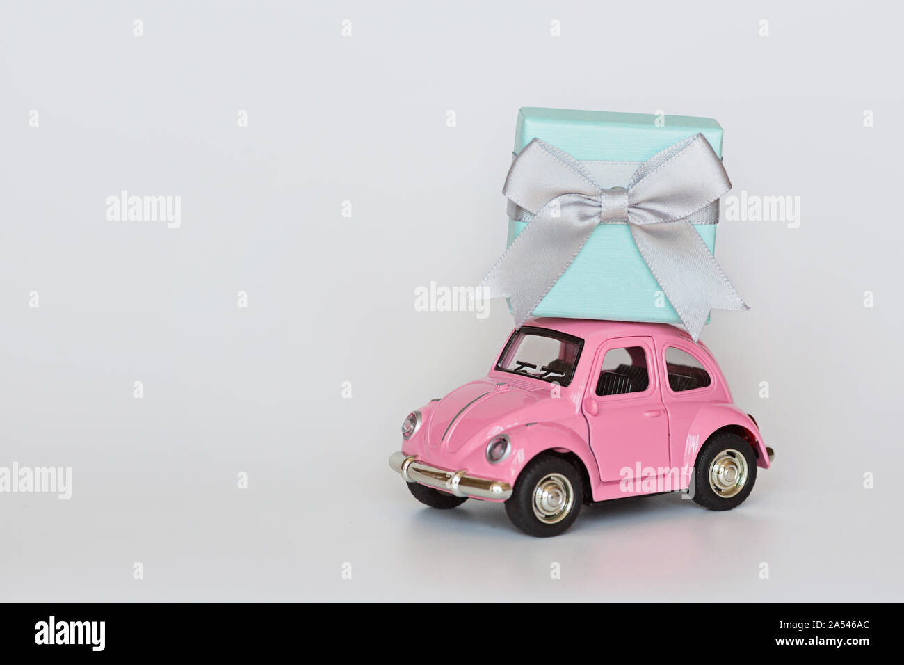 Changxing, China - October 15, 2019: Pink retro toy car delivering gift box on roof on white background. Valentine day February 14, International Stock Photo